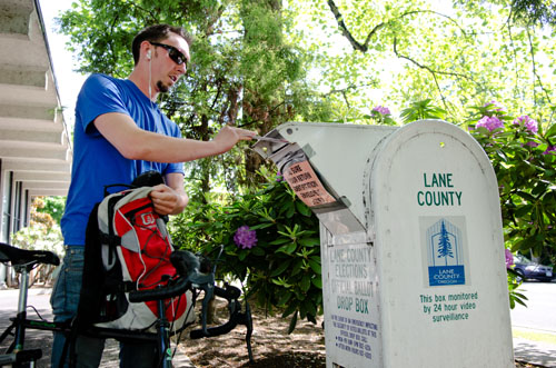 Jason Randall, 26, places his mail-in ballot in a drop box outside the Lane County Elections Office in Eugene, Ore. Michael Ciaglo/News21