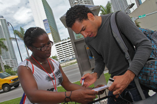 Barbara Johnson, a National Council of La Raza voter registration canvasser, assists Quilvio Rodriguez, 26, of Miami, with his registration application on May 31, 2012, outside a grocery store in Miami's Little Havana neighborhood. Photo by Ethan Magoc/News21